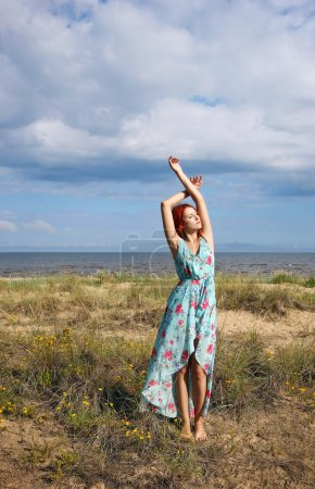The redhead girl standing at the sea shore in light long dress