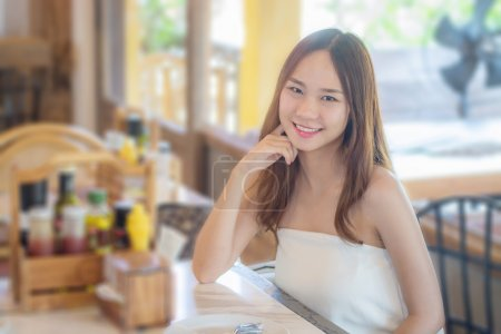 Asia woman sitting in restaurant with smile as restaurant backgr