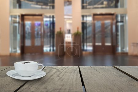 Defocus with terrace wood and cappuccino coffee with elevators in shopping mall for background usage