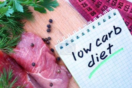 Photo pour Bloc-notes avec régime pauvre en glucides et viande fraîche sur la planche en bois - image libre de droit