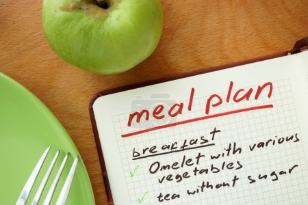 Notepad with words  meal plan with apple. Weight lose concept.