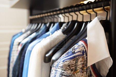 Photo pour Vêtements sur cintres dans le magasin. Ferme là. Dof peu profond - image libre de droit