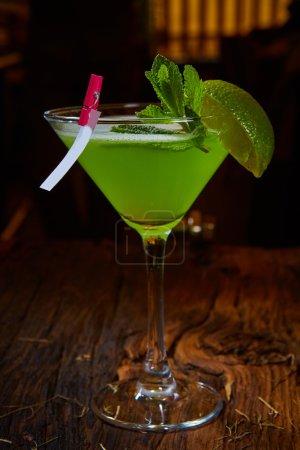Photo pour Verre à martini avec cocktail avec des feuilles de citron vert et de menthe verte - image libre de droit
