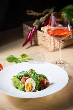plate of spring mix salad with strawberry, eggs and tuna