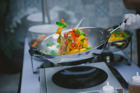 Photo for Chef cooking vegetables in wok pan. Shallow dof - Royalty Free Image