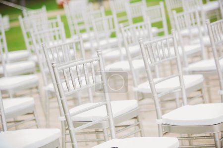Photo pour Avant une cérémonie de mariage, les chaises blanches sans fin attendent pour leurs invités. - image libre de droit