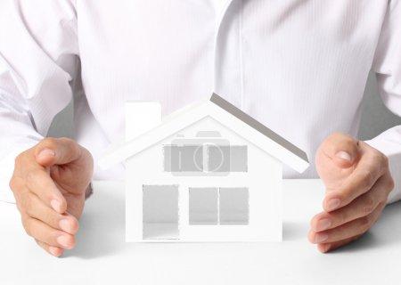 Photo pour Concept d'assurance de biens, homme protéger le modèle de la maison - image libre de droit