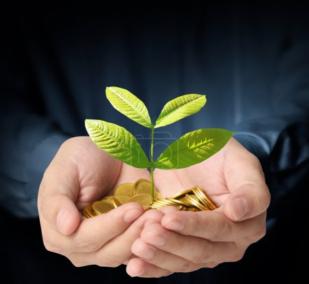Photo for Businessman holding plant sprouting from a handful of coins - Royalty Free Image