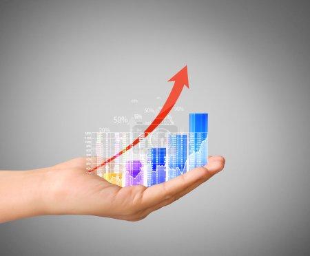 Photo pour Concept d'investissement avec des symboles de tableau financier provenant d'une main - image libre de droit