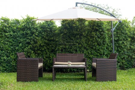 Set of rattan garden furniture under a big garden umbrella isolated on white with clipping path