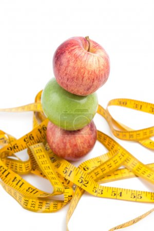 healthy diet concept , apple and a measuring tape on white background