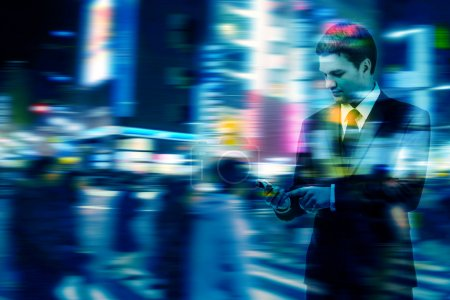 Photo for Double exposure of businessman uses the smart phone on the city street, and motion blur background - Royalty Free Image