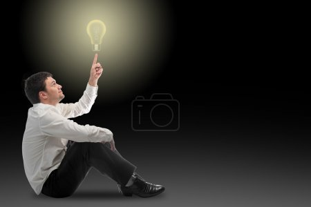A young businessman sitting on the floor thinking up new ideas