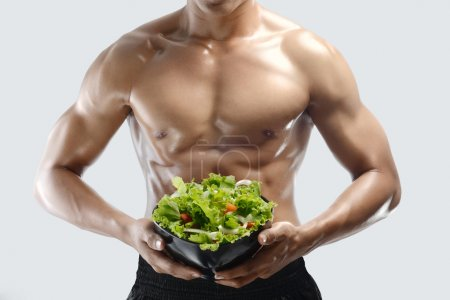 A muscular guy and fresh Salad bowl,shaped abdominal, isolated