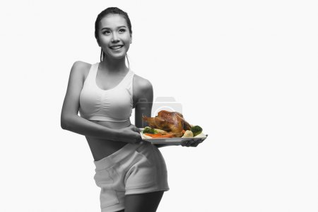 Photo for Young woman with perfect body holding and showing roast chicken - Royalty Free Image