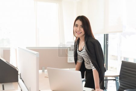 smiling female executive leaning on desk in office