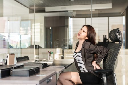 Young businesswoman having back pain while sitting at office des