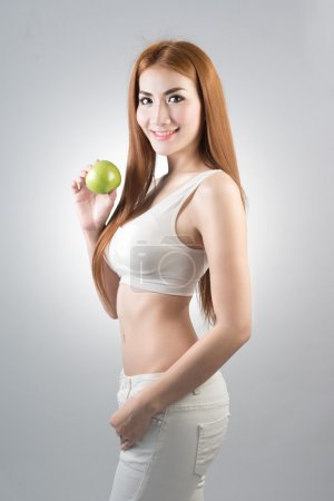 healthy weight loss concept,Smiling beauty holding green apple while on gray background,with clipping path