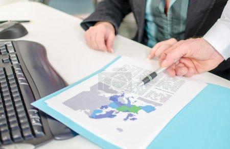 Businessman showing an economic document with a pen