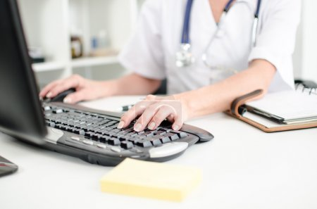 Female doctor taping on a computer keyboard