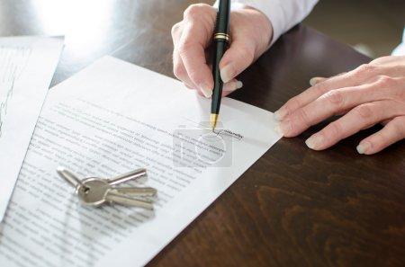 Photo pour Signature d'un contrat de biens immobiliers sur un bureau de femme - image libre de droit