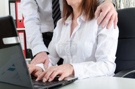 Manager putting his hand on the shoulder of his secretary
