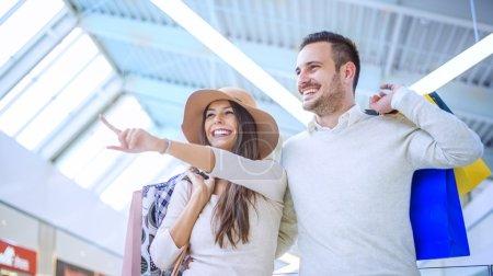 Foto de Feliz pareja joven con bolsas de la compra. Imagen tomada en un centro comercial. Disfrutar juntos y tener un gran tiempo. - Imagen libre de derechos