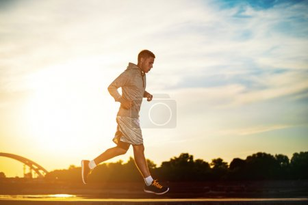 Photo for Man running outdoors on a sunny day.Young male jogger athlete training and doing workout outdoors in city. - Royalty Free Image