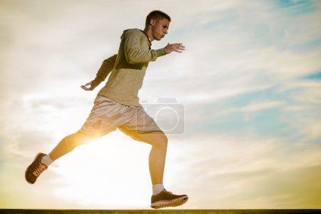 Photo pour Athlète de jeunes mâles jogger formation et faire la séance d'entraînement en plein air dans la ville. Environnement extérieur urbain remise en forme et exercice. - image libre de droit