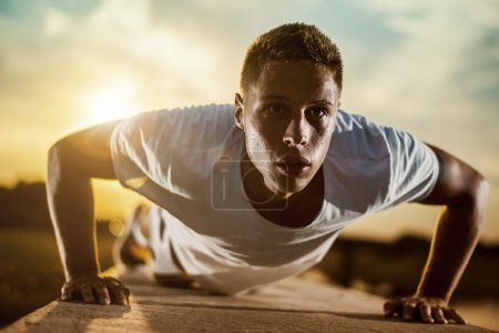 Photo for Young male jogger athlete training and doing workout outdoors in city. Fitness and exercising outdoors urban environment. - Royalty Free Image