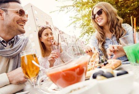 Photo pour Jeune groupe de rire personnes mangeant des pizza et s'amuser. Ils profitent de manger et de boire ensemble - image libre de droit