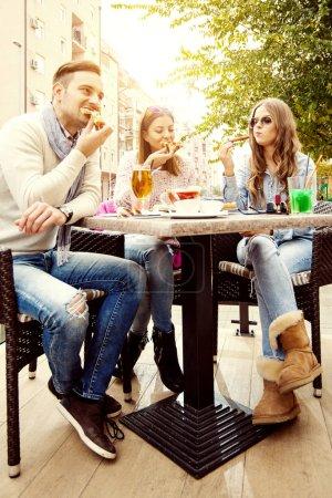 Photo pour Jeune groupe de personnes mangeant de la pizza et s'amusant. Ils aiment manger et boire ensemble . - image libre de droit