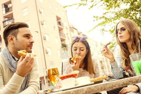Photo pour Amis de manger la pizza et de s'amuser. Ils profitent de manger et de boire ensemble - image libre de droit