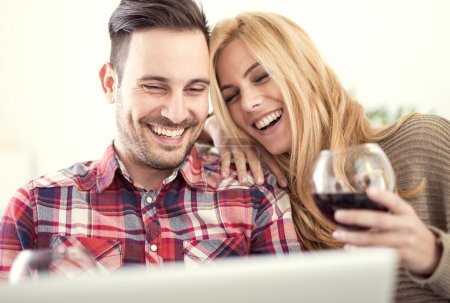 Photo for Close up of a young couple enjoying wine at home.They are sitting close to each other and drinking red wine.Love concept. - Royalty Free Image