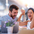 Image of young loving couple sitting in cafe, usin...