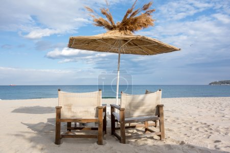 Beach chair and straw umbrella on sand beach with cloudy blue sky