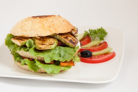 Vegetarian burger with zucchini, carrots, tomato and cucumber