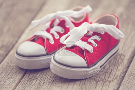 Red baby sneakers on wooden background. Vintage style image