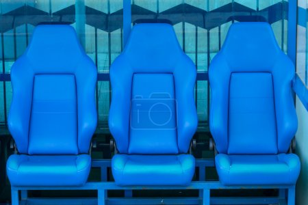 Empty coach and reserves blue bench on a football stadium
