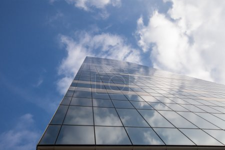 Modern office building on sky background with clouds reflection