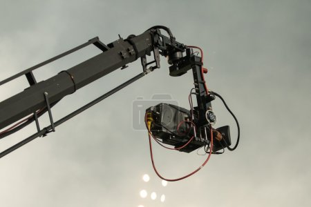 TV camera on a crane on football mach or concert