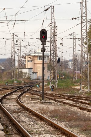 Red semaphore and railway tracks. Traffic light shows red signal on railway