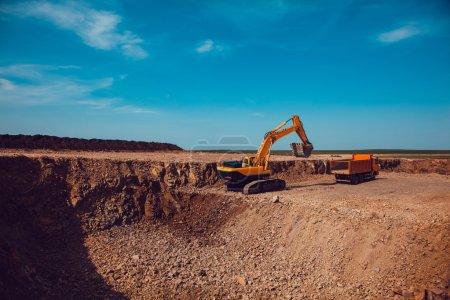 Photo pour Une excavatrice charge du gravier dans un camion sur une carrière de pierre concassée - image libre de droit