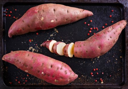 Red Sweet potato over rustic metal tray