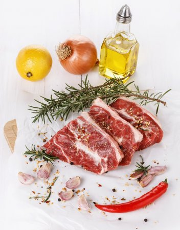 Red meat, vegetables and spices over white background