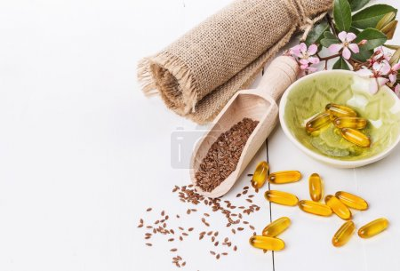 Linseed and flaxseed oil capsules over white background