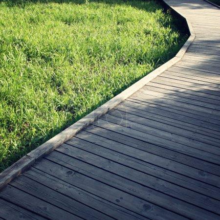 Chemin en bois dans un parc de printemps. Photo âgé