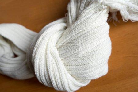 Photo pour Une écharpe blanche tricotée forme un motif abstrait. Vêtements d'hiver chauds. Texture laine - image libre de droit