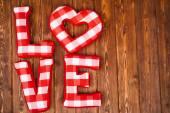 Láska slovo plyš červenými písmeny na pozadí. Plné kostkovanou textilií