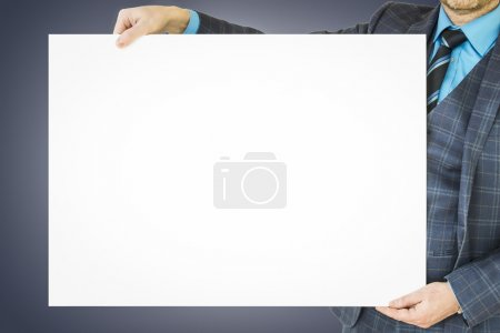 Business man holding poster with room for text and graphic.